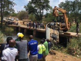People attend to a vehicle that fell off Mtshabezi Bridge which runs over Mtshabezi River in Gwanda in this file photo